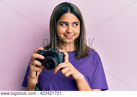 Young latin woman using reflex camera smiling looking to the side and staring away thinking.