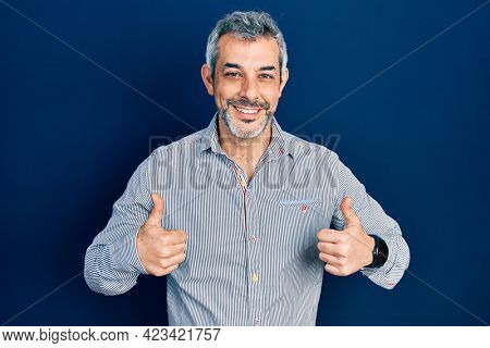 Handsome middle age man with grey hair wearing business shirt success sign doing positive gesture with hand, thumbs up smiling and happy. cheerful expression and winner gesture.