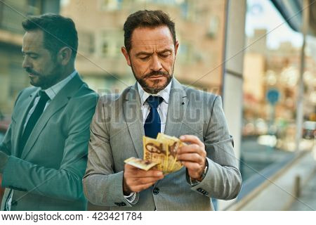 Middle age businessman with serious expression counting hungarian forint banknotes at the city.