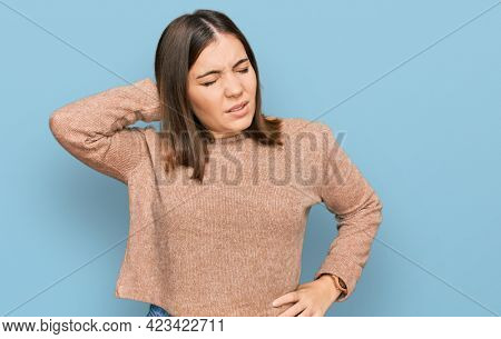 Young beautiful woman wearing casual clothes suffering of neck ache injury, touching neck with hand, muscular pain