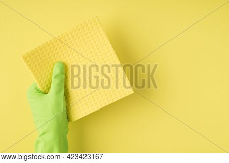 Above Pov Photo Of Reusable Cleaning Cellulose Sponge And Green Gloves Isolated On The Yellow Backgr