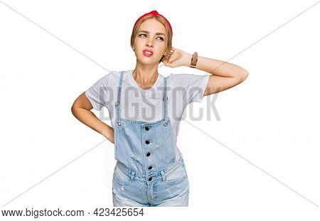 Young caucasian girl wearing casual clothes suffering of neck ache injury, touching neck with hand, muscular pain