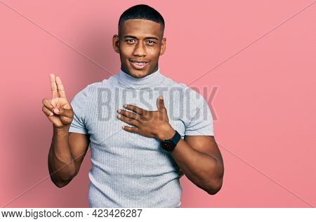 Young black man wearing casual t shirt smiling swearing with hand on chest and fingers up, making a loyalty promise oath