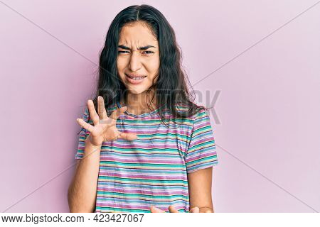 Hispanic teenager girl with dental braces wearing casual clothes disgusted expression, displeased and fearful doing disgust face because aversion reaction. with hands raised
