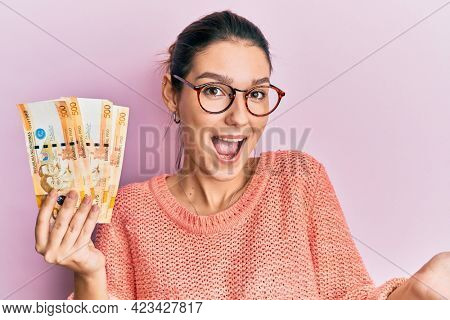 Young caucasian woman holding 500 philippine peso banknotes celebrating achievement with happy smile and winner expression with raised hand