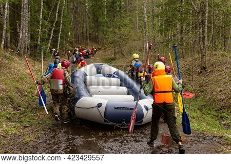 Petrozavodsk, Russia - May 16th, 2021: Group Of Tourists Are Carrying The Rubber Raft Along The Shor