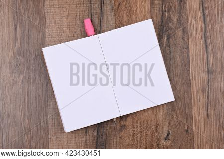 Open writing pad with a pencil underneath. High angle shot on a wood background. The pads pages are blank.