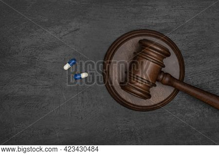 Judge Gavel And Two Pills. Illegal Use Of Drugs. Pharmaceutical Lawsuit. Black Background.