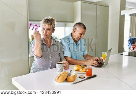 Middle age caucasian couple eating breakfast at home using laptop annoyed and frustrated shouting with anger, yelling crazy with anger and hand raised
