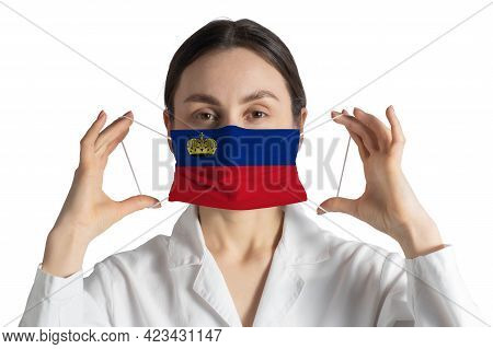 Respirator With Flag Of Liechtenstein Doctor Puts On Medical Face Mask Isolated On White Background.