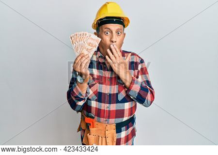 Senior hispanic man wearing handyman uniform holding turkish liras covering mouth with hand, shocked and afraid for mistake. surprised expression