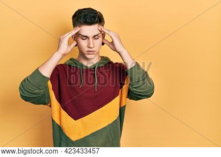 Young caucasian boy with ears dilation wearing casual sweatshirt with hand on head for pain in head because stress. suffering migraine.