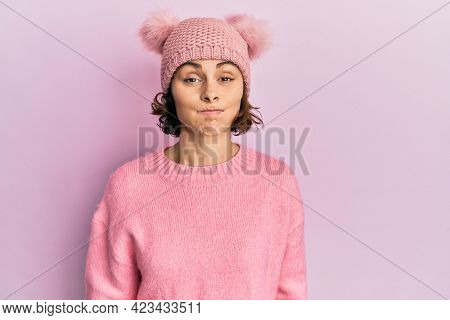 Young brunette woman wearing cute wool cap puffing cheeks with funny face. mouth inflated with air, crazy expression.
