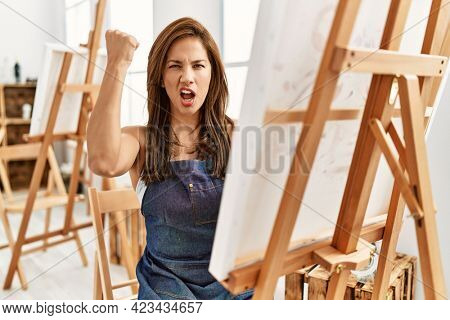 Young latin artist woman painting at art studio annoyed and frustrated shouting with anger, yelling crazy with anger and hand raised