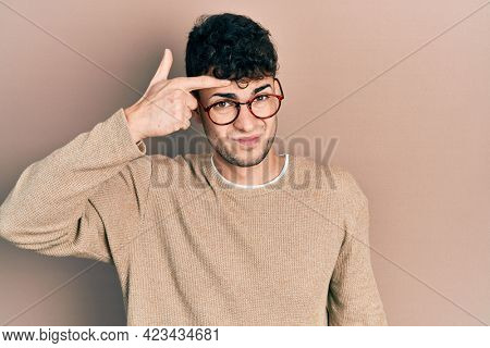 Young hispanic man wearing casual clothes and glasses pointing unhappy to pimple on forehead, ugly infection of blackhead. acne and skin problem