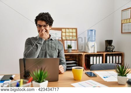 Young hispanic man wearing business style sitting on desk at office smelling something stinky and disgusting, intolerable smell, holding breath with fingers on nose. bad smell