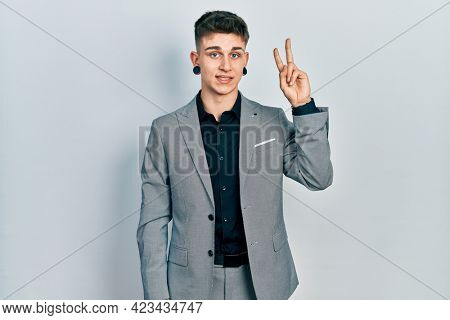 Young caucasian boy with ears dilation wearing business jacket showing and pointing up with fingers number two while smiling confident and happy.
