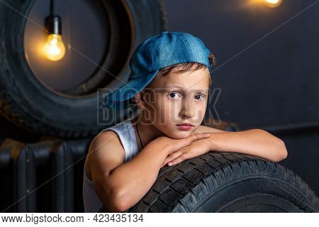 Portrait Of A Caucasian Serious Boy 7 Years Old, In A Denim Cap, Dressed On The Side, Leaning On The