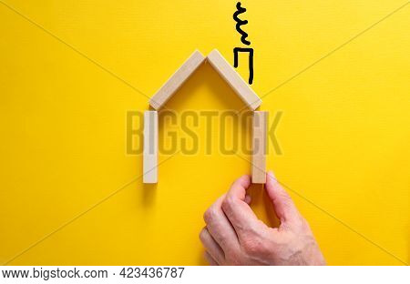 Realt Estate Planning Symbol. Businessman Builds A Model Of A Wooden House From Wooden Blocks. Copy