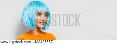 Studio Portrait Of Young Pretty Girl With Blue Hair Bob Wearing Orange Sweater On White Background.