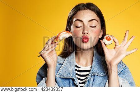 Glamour Girl Holds Sushi Rolls And Sashimi With Chopsticks, Making Kissing Face, Eating Favorite Mak