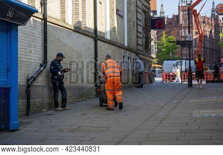 Nottingham, Nottinghamshire, England- June 1, 2021. Street Sweeper On His Back Dressed In Hi Vis Ora