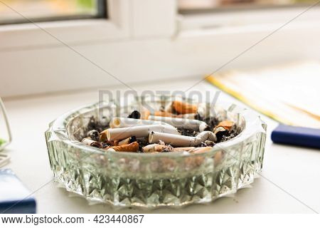 Glass Ashtray With Cigarette Butts In Sunlight Close Up