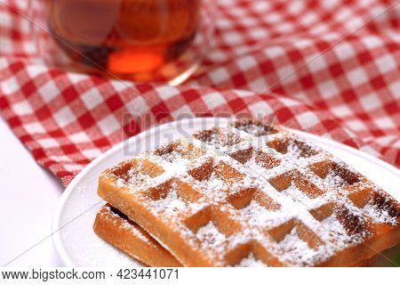 Homemade Cakes - A Recipe For Belgian Waffles Sprinkled With Powdered Sugar On A Checkered Tableclot