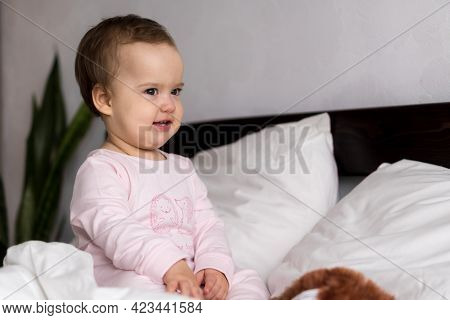 Authentic Portrait Caucasian Little Infant Chubby Baby Girl Or Boy In Pink Sleepy Upon Waking Lookin
