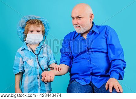 Grandson In Medical Mask Play Doctor With Grandpa. Medicine. Emergency. Home Treatment.