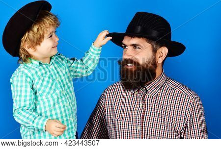 Fathers Day. Happy Dad With Son In Checkered Shirts And Fashionable Hats. Parenthood Concept.