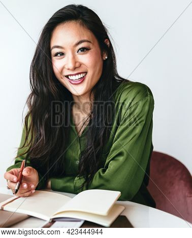 Happy woman writing a journal in her office