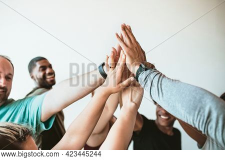 Cheerful people doing a group high five