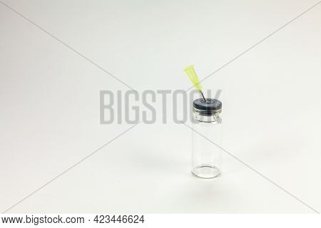 White Background And Several Glass Vaccine Bottle With Surgical Needle