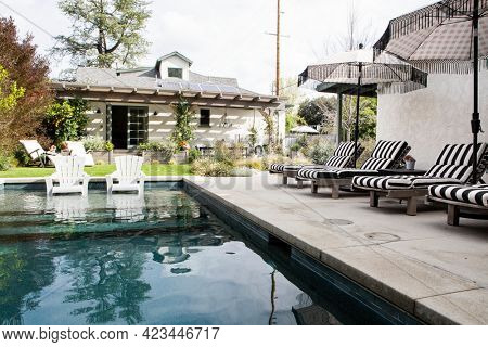 Wooden seats by a pool with parasols