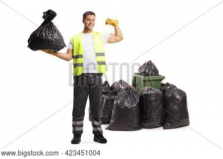 Full length portrait of a waste collector holding a bag and showing muscles in front of a bin isolated on white background