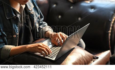 Croped Shot Male Hands Typing On Laptop Keyboard On While Sitting On Sofa In Vintage Room.