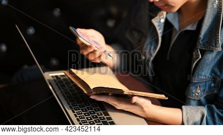 Young Man Searching Information Data On Internet Networking With Smartphone And Laptop On Sofa.