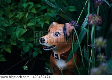 Cute Ceramic Dog Figurine. Spring Garden After Rain With Garden Statue. Dark Natural Background, Sof