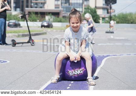 The Child Is Jumping On A Fitball. Street Games For Children. The Joyful Girl Quickly Jumps On The B