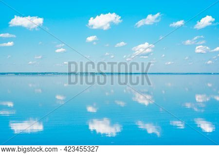 Mirror Reflection Of Clouds In Lake Water. Clouds In Blue Sky And Reflection In Large Lake. Big Beau