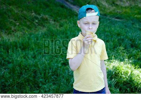 Cute Boy Eating Ice Cream Cone With Stains Around His Mouth. High Quality Photo