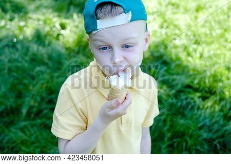 Portrait Boy Eating Ice Cream With Stains Around His Mouth, In The Park