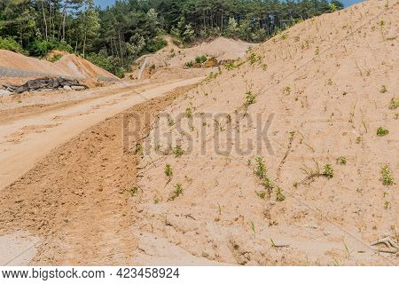 Backhoe Tracks In Red Dirt Going Uphill At Construction Site.
