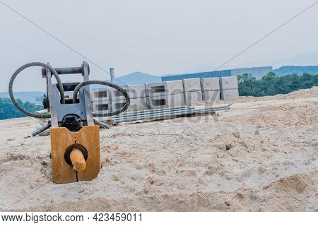 Jackhammer Attachment For Backhoe Laying On Ground At Construction Site.