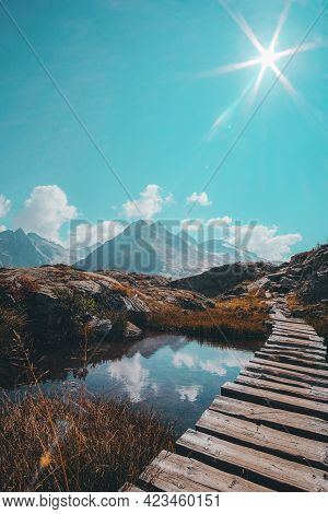 A Vertical Shot Of A Narrow Wooden Passage Over A Reflective Small Lake And A Mountain Range On The