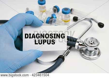 Medicine And Health Concept. A Stethoscope And Ampoules Lie On A White Background, The Doctor Holds