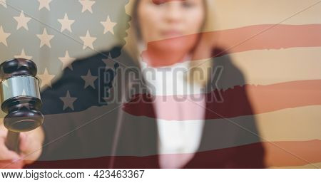 Waving american flag against caucasian female judge knocking a gavel in the court room. american judiciary and law concept