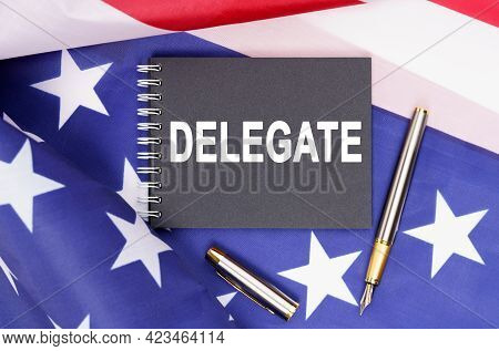American Concept. The Us Flag Has A Pen And A Notebook With The Inscription - Delegate