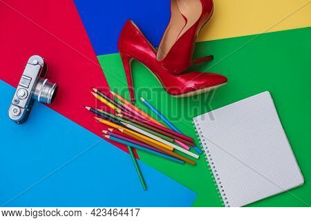 Beautiful Womens Shiny Patent Purple Stiletto Heels, Pencils, Notebook And Old Retro Camera On A Col